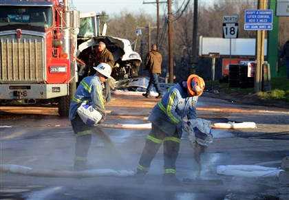 Canton crash 4 Absorbent material is spread on the surface of Route 18 after the spill from a rig carrying diesel fuel crashed with two tankers.