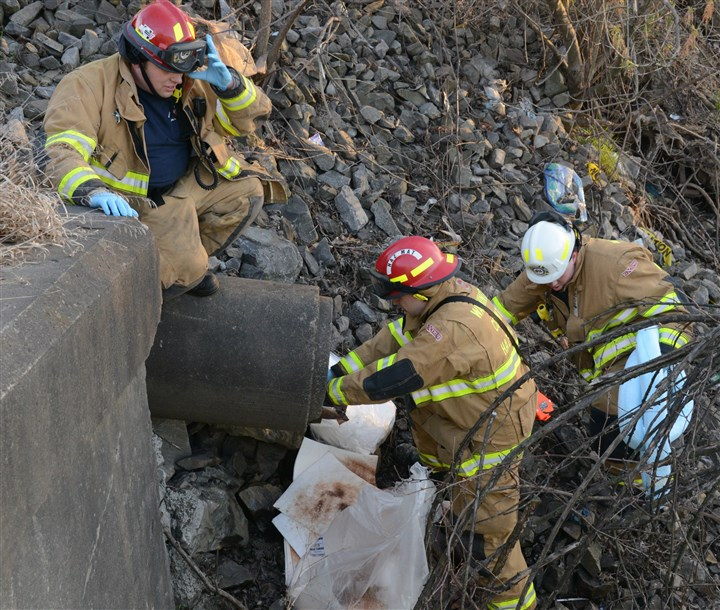 20140421dsSpillLocal04-5 Firefighters handle some of the diesel fuel runoff from a drain leading into Chartiers Creek after a rig carrying diesel fuel collided with two tankers carrying fracking fluids on Henderson Avenue/Route 18 in Canton. Some fracking fluid also flowed into the creek. Two of the three drivers were hospitalized.