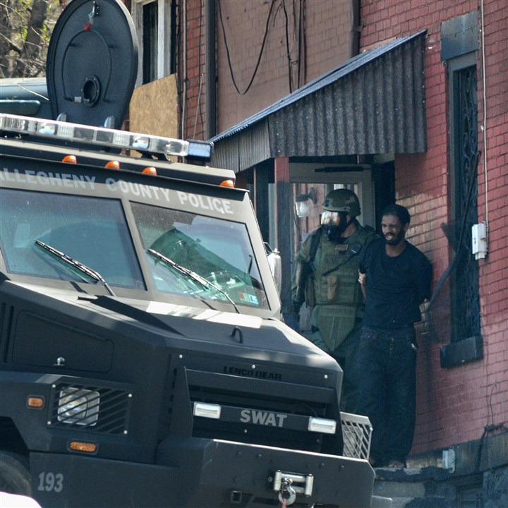 20140414radSWATLocal02 SWAT team officers remove a suspect from a building at 47 Pride St. Monday morning.