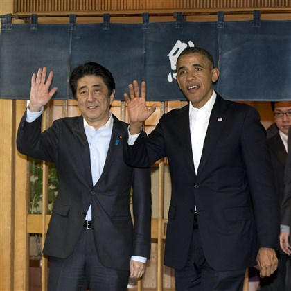 Japan Obama Asia President Barack Obama and Japanese Prime Minister Shinzo Abe wave to media as they depart Sukiyabashi Jiro sushi restaurant in Tokyo Wednesday.