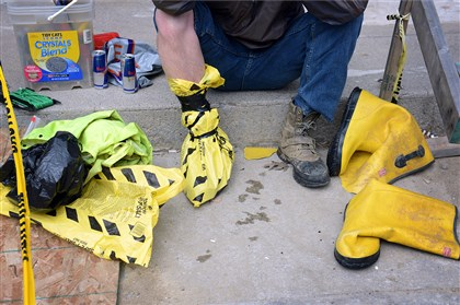 Carrick apartment sewage A worker who did not want to be identified puts bags on his feet on Wednesday to avoid getting sewage on his skin before he snakes out a blocked sewage line affecting a set of apartments in Carrick near Brownsville Road and Churchview Avenue.