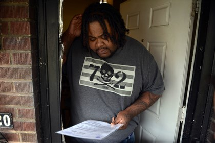 20140425MWHevictionLocal01 Nate Miliner, 27, of Carrick, looks over an Allegheny County order to vacate his Berg Place apartment on Friday.