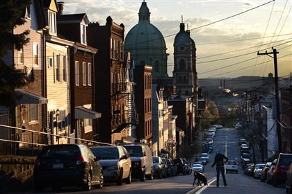 20140426bwPolishLocal01 Kate Bazis of Wilkinsburg walks her daughter Gaia Parrish's dog Corazon across Brereton Street in Polish Hill.