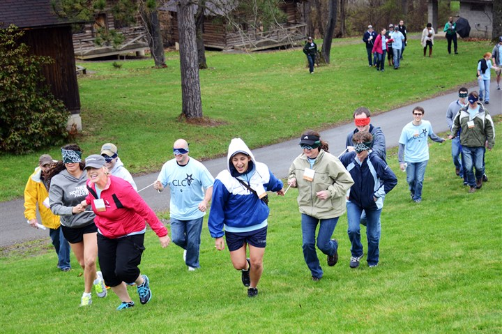 20140425lfVeteranLocal02-1 Susanne Kokoska, left, (red jacket) of North Huntingdon, and Ariana Pourmonir, (white and blue jacket) of the Hill District lead a pack of veterans through a obstacle course during a trust exercise on Friday at YMCA Camp Kon O Kwee in Fombell.