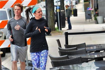 Marathon training couple Meg Coyne, right, a waitress at Mad Mex in Shadyside on South Highland Avenue, gives a thumbs up to someone in the restaurant as she and her boyfriend, Jake Trethewey, a line cook at Legume, train April 28 for the Pittsburgh Marathon.