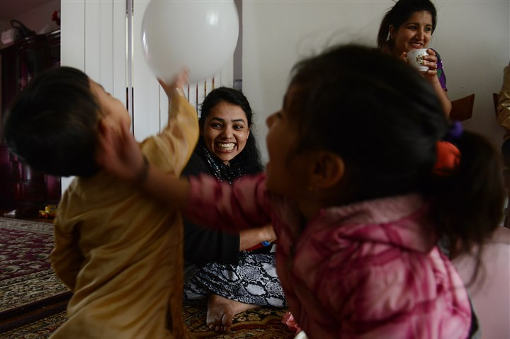 Bhim Maya Poudel inflates balloons Bhim Maya Poudyel, center, inflates balloons for Apson Thapa, 3, left, and Perika Poudel, 4, before a family birthday party Monday at her apartment in Carrick.