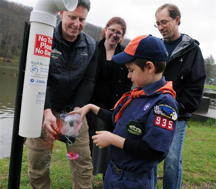20140428JHNorth Container02 Robert Habegger, left, Dawn Miller, Eric Filo, and Logan Southwick, 7, center, collect used fish lines from new containers at North Park Lake.