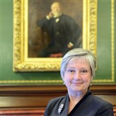 Jo Ellen Parker in her new office in front of a portrait of Andrew Carnegie.