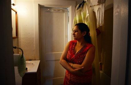 201400428jrCarrickfollowLocal5-4 Indira Dhaurali, 36, stands in her bathroom on Monday, April 28, in Carrick. A rock thrown through her bathroom window left a large hole that has gone unrepaired for more than a month. She said she has called the landlord more than four times.