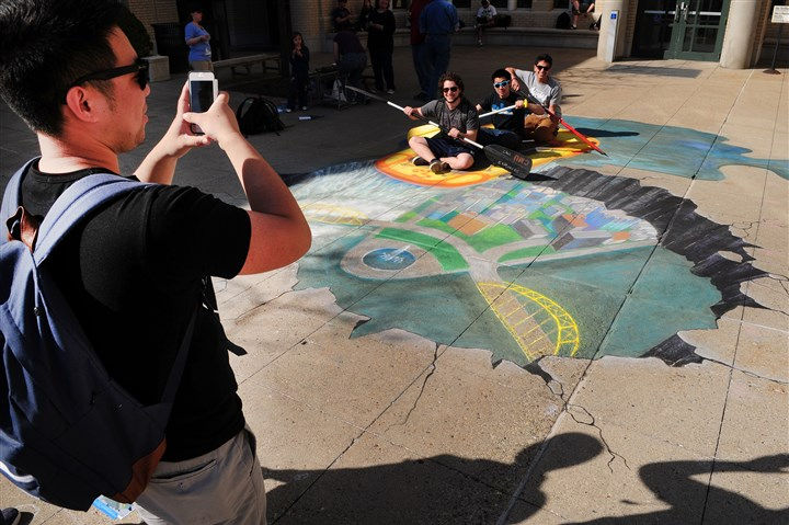 CMU students Carnegie Mellon student Kevin Louie takes a picture of fellow students Dan Kelley, Dale Zhang and Mahir Kothari interacting with a 3D chalk drawing on the sidewalk outside of the Carnegie Mellon University Center.
