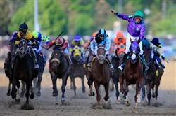 California Chrome, ridden by Victor Espinoza, crosses the finish line to win the 140th running of the Kentucky Derby at Churchill Downs on May 3, 2014 in Louisville, Kentucky.