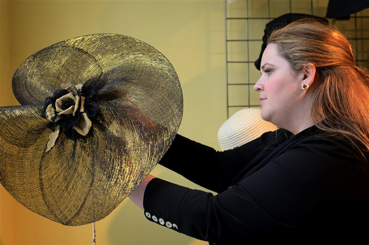 "Asbury Fine Hats Jessica Sacks, owner of Asbury Fine Hats in Squirrel Hill, adjusts a hat on its display rack. ""I love hats. There was a need for [a hat store] in the community,"" Ms. Sacks said."