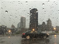 Rain collects on the windshield as a car drives on Crawford Street, and the US Steel Tower looms in the background.