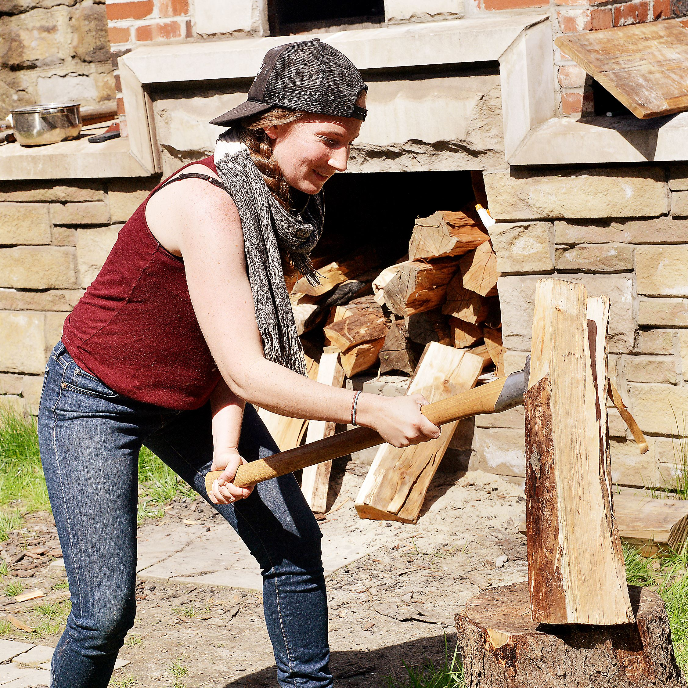 20140506lrchopwoodstandalone02 Shauna Kearns, 25, a student in Chatham University's food studies program, chops wood at the Braddock community brick oven to feed the fire for her sourdough bread.