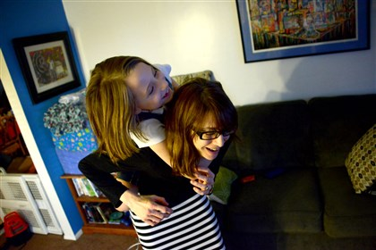 Dawn Patton Mangine gives her daughter, Kate Dawn Patton Mangine gives her daughter, Kate, a piggyback ride inside their Coraopolis home.