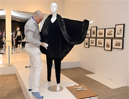 "Warhol Halston exhibit Stephane Houy-Towner, a consulting curator, dresses a mannequin in a Halston silk velvet, fox fur-trimmed cape for the ""Halston and Warhol: Silver and Suede"" exhibit."