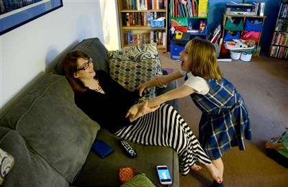 Dawn Patton Mangine and daughter Kate Dawn Patton Mangine of Coraopolis plays with her daughter Kate, 7, at their home Wednesday. Not pictured are her other children, Michael, 3, and Flora, 9.