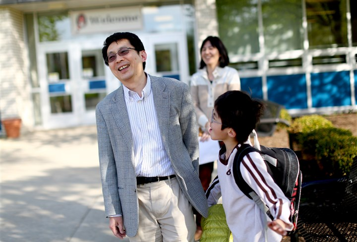"Tai Sing Lee and his son Harrison Tai Sing Lee, a Carnegie Mellon University researcher and a new citizen, picks up his son, Harrison, from O'Hara Elementary School in O'Hara. ""I want my children to love America,"" said Mr. Lee, who typifies the highly educated Asian residents who have dominated Pittsburgh's recent immigration trends."