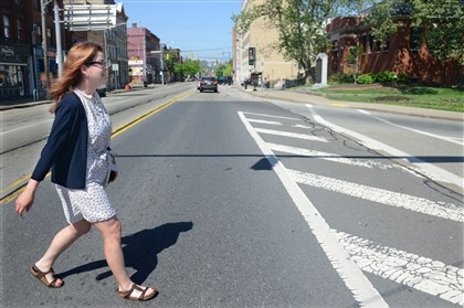 20140513dsSusanWaldoBiz02 Suzy Waldo crosses East Carson Street on Tuesday on her way to the Carnegie Library's South Side Branch. She walks five blocks from her home to work.