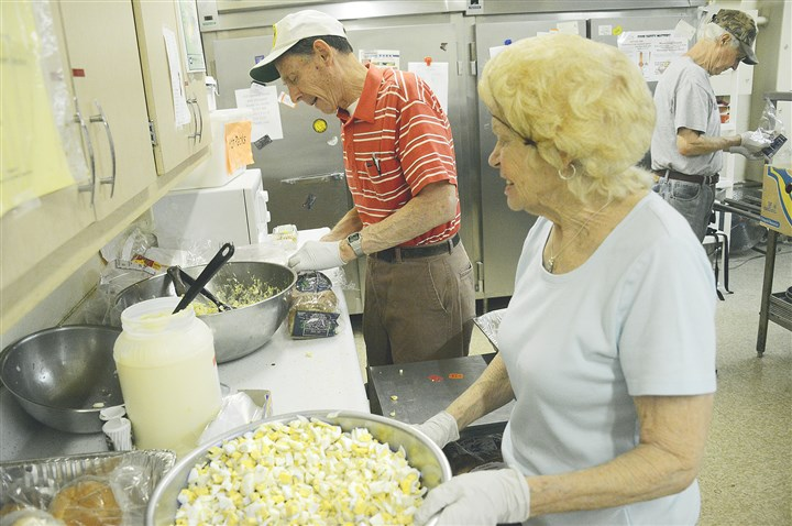 20140509lfMealsWest02-1 Volunteers for Southwest Meals on Wheels program Larry Berner, left, and Fern McDonough, prepare lunches at St. John Lutheran Church in Carnegie on Friday.