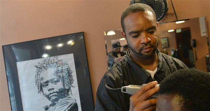 Clipping hair at The Natural Choice Elbro Yelverton, a barber at The Natural Choice in Oakland, uses clippers to shape the natural look of a woman's hair.