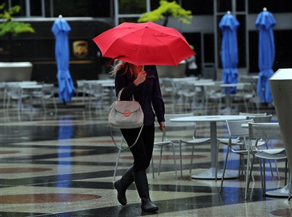 20150515JHLocalRainArt01 A pedestrian walks in the rain across PPG Plaza, Downtown, on Thursday.