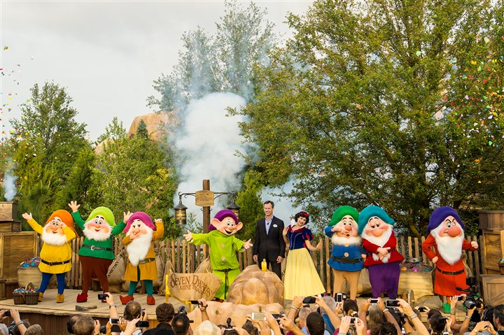 "20140516hdMineRide04Mag-3 Tom Staggs, chairman of Walt Disney Parks and Resorts, joins Snow White the Seven Dwarfs in the Magic Kingdom at Walt Disney World Resort in Lake Buena Vista, Fla., to dedicate the park's newest attraction, the Seven Dwarfs Mine Train. The attraction, which will open to guests Wednesday, is a family-style coaster that immerses riders in scenes inspired by the classic film ""Snow White and the Seven Dwarfs."" The attraction completes New Fantasyland, the largest expansion in the Magic Kingdom's history."