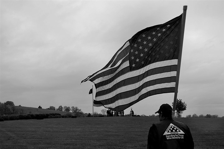 20150515lrvetburial20 A veteran and member of the Patriot Guard Riders unfurls his American flag.