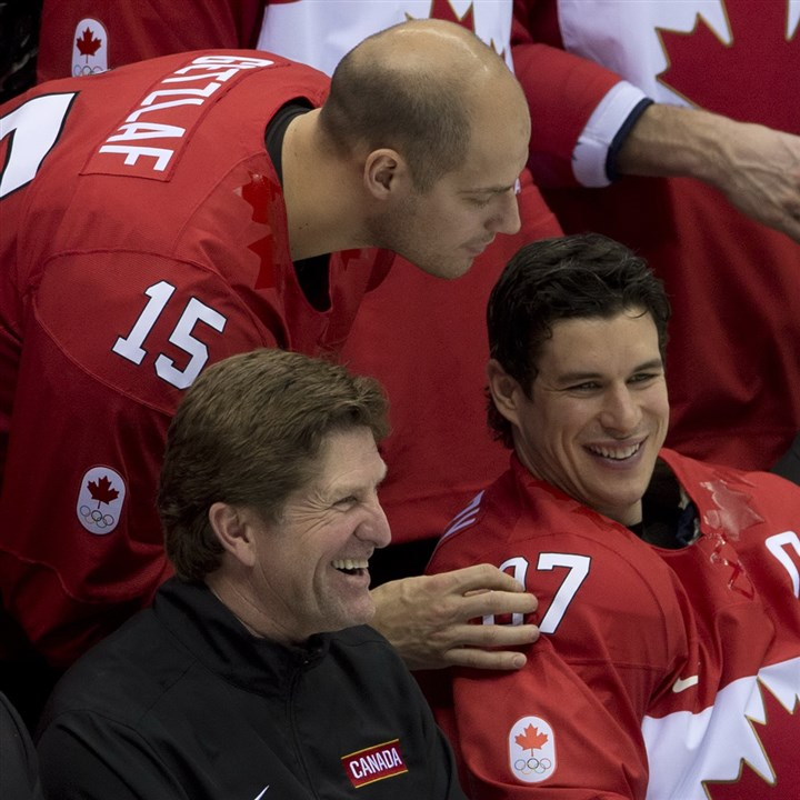 babcock0520 Team Canada's Ryan Getzlaf looks over the shoulder of Sidney Crosby, head coach Mike Babcock, left, and General Manager Steve Yzerman during the team photo at the start of practice at the Sochi Winter Olympics, Tuesday Feb. 11, 2014, in Sochi, Russia.