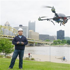 "20140520dDemoDayBiz01 Dick Zhang, CEO of Identified Technologies, flies one of their ""drones"" on the North Shore. The drone is a flying robot to customized to collect images, data or gas readings."