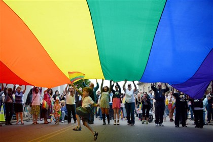 20140520MWHequalityLocal11-6 Elijah Socie, 6, of Brookline, runs underneath a large pride banner while carrying a pride flag to celebrate a federal judge ruling Pennsylvania's ban on same-sex marriage unconstitutional held on Ellsworth Avenue in Shadyside on Tuesday.