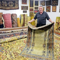 Wade Shehady, owner of Shehady's Oriental Rugs  Wade Shehady, owner of Shehady's Oriental Rugs in Aspinwall, shows a Heriz rug from the early 19th century.