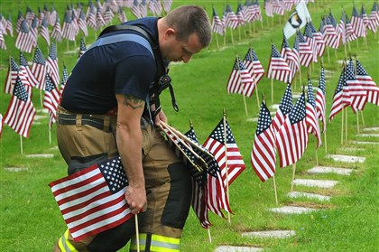 20140521lrmemorialflagstandalone08-7 Pittsburgh firefighter Brad Bennett plants flags on the graves of veterans in Allegheny Cemetery, for the upcoming Memorial Day holiday.