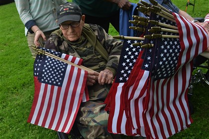 20140521lrmemorialflagstandalone09-8 Paul Klimovich, 92, a resident of Schenley Gardens, a senior living facility in Oakland, holds flags which will be placed on veterans' graves in Allegheny Cemetery for the upcoming Memorial Day holiday. Mr. Klimovich served in the army in World War II and landed on Utah Beach during the D-Day invasion.