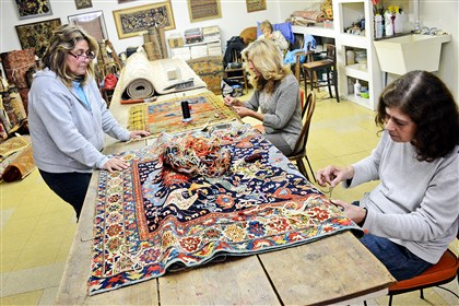 20140520RugMag02-1 Kim Volzer, left, her sisters, Janet Knight, and Pam Smith, works on reweaving a rug at Shehady's Oriental Rugs in Aspinwall.