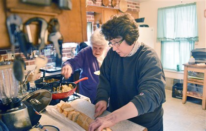 Dearheart cooking Carol Pascuzzi, right, cuts bread for dinner in her Turtle Creek kitchen while her mother, Kathleen, 82, loads up a plate from the stove.