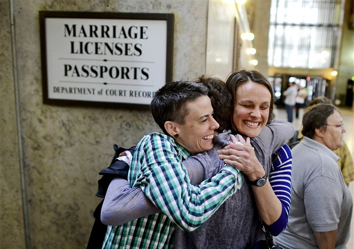 20140521MWHlicensesLocal01 The day after a federal judge ruled Pennsylvania's same-sex marriage ban unconstitutional, Jess Garrity, left, and Pamela VanHaitsma, right, hug their friend Jamie Phillips, center, while standing first in line to apply for a marriage license inside the City-County Building in Downtown Pittsburgh.