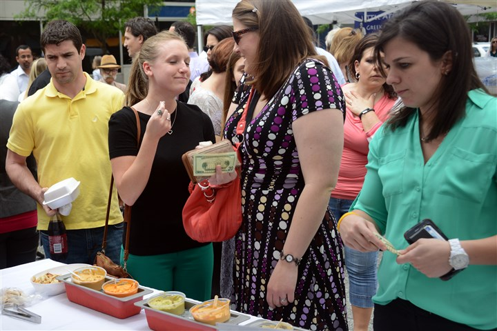 20140522MarketPress01 Sarah Thomas, 23, left, enjoys the taste of Hello Hummus' dip while co-worker Melinda DelPrince, 27, looks on at the Market Square Farmers Market today Downtown.