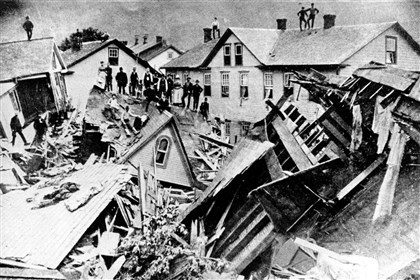 johnstownFloodFile-3 People stand atop a mass of destroyed houses that had been compressed by the force of floodwaters on May 31, 1889.