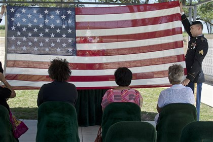 Berlanga family service Members of a U.S. Army honor guard fold an American flag presented to Anita Berlanga, seated at left.