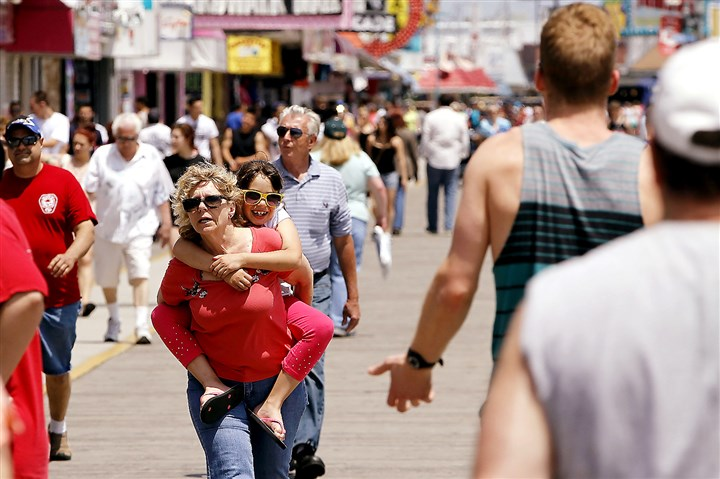 SummerTravel02-1 Marie Midiri of Downingtown, Pa., gives her granddaughter, Feliciana Midiri, 7, a ride on her back as they stroll the Wildwood, N.J. boardwalk Friday.
