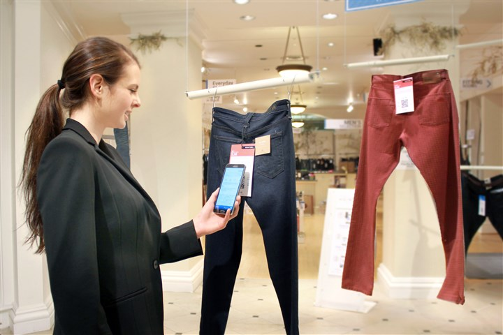 Future of Shopping In this undated photo provided by Hointer, a woman demonstrates the Seattle store's shopping technology. Hointer displays clothing not in piles or on racks but as one piece hanging at a time, like a gallery. Shoppers just touch their smartphones to a coded tag on the item and then select a color and size via their phone. By the time a shopper is ready to try them on, they're already at the dressing room.