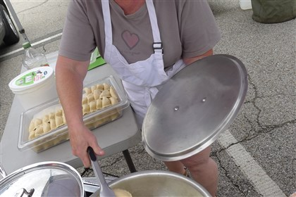P1230777-7 Terry Smith-Rawecki fires up a batch of pierogies and onions at the Gosia's Pierogies booth at opening day at the Upper St. Clair Farmers Market on May 29.