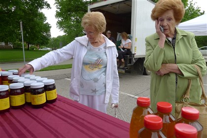 P1230754-1 Early birds Mary Pursglove, left, and Toni Petrucci of Mt. Lebanon check out the goods at opening day at the Upper St. Clair Farmers Market on May 29. Mrs. Petrucci, a farmers market regular, took a call on her cell phone from her granddaughter and she asked her what produce she wanted her to bring her.
