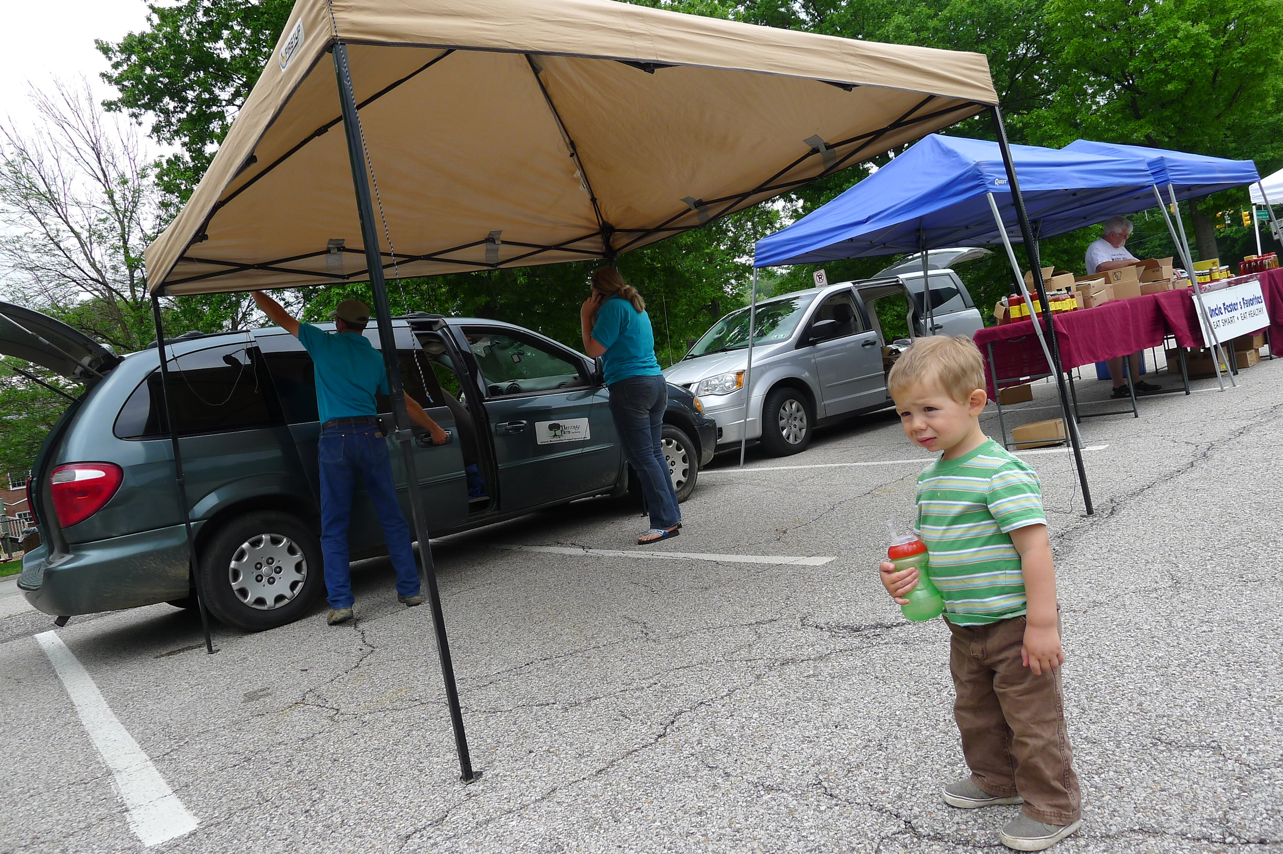 P1230750 2-year-old Micah Burns watch as his parents, Pete and Tara Burns, set up their Heritage Farm booth after driving all the way down from Ridgway at opening day at the Upper St. Clair Farmers Market on May 29.