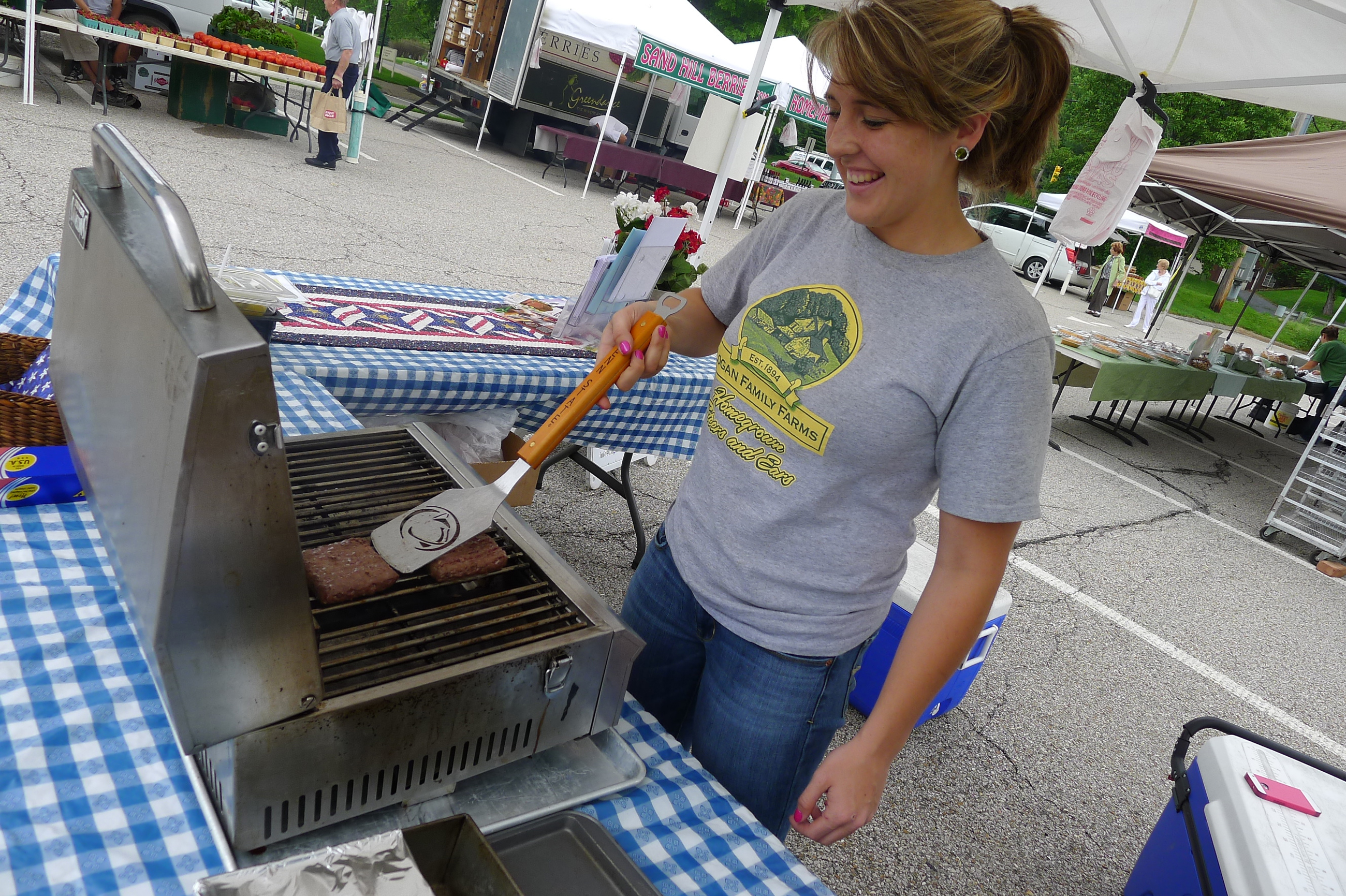 P1230787-8 Logan Farms worker Brittany Coles starts cooking burgers early, in part because she wants to eat one herself at opening day at the Upper St. Clair Farmers Market on May 29.