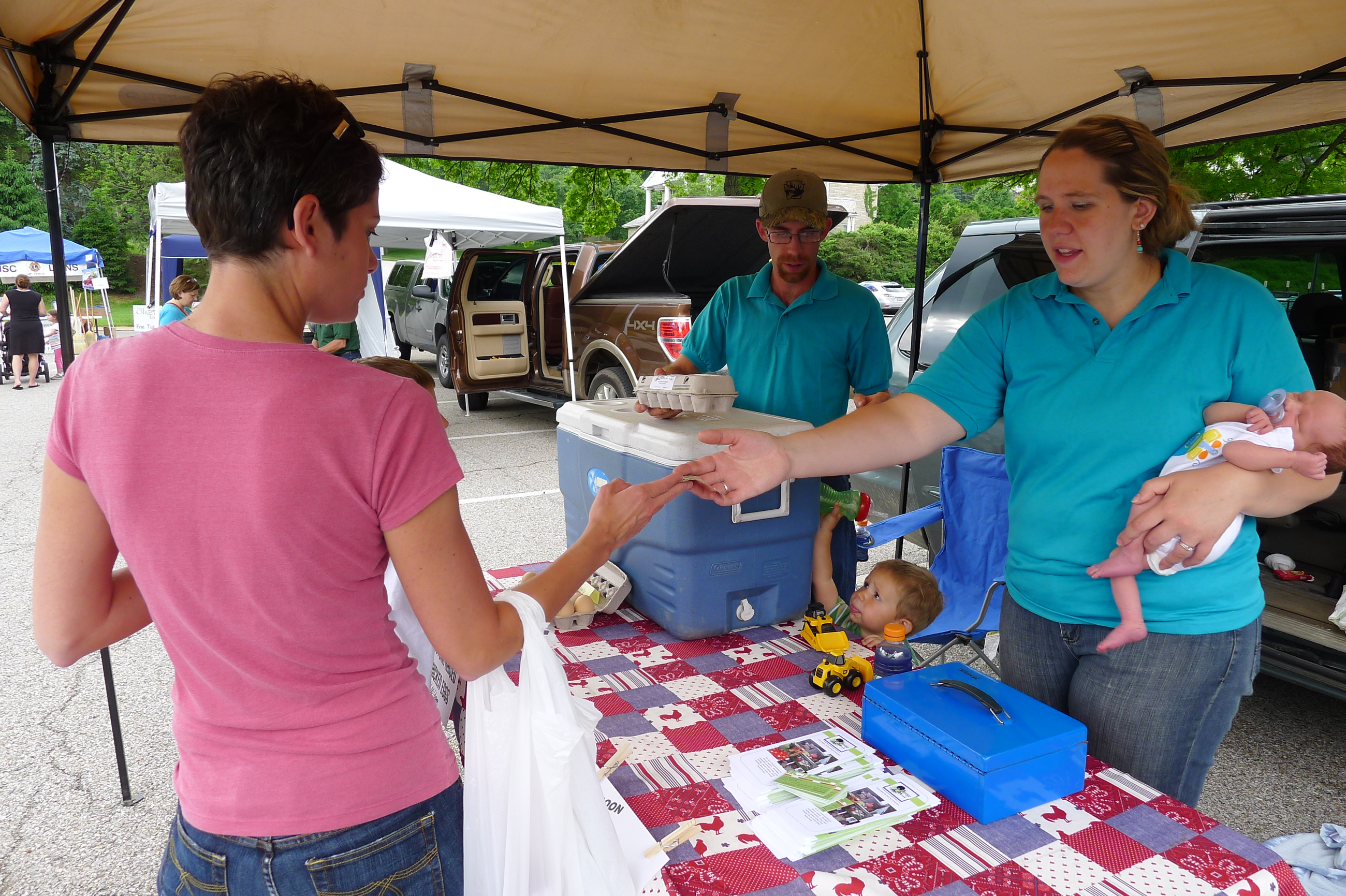 P1230865-17 Tara Burns held 10-day-old Patrick in one arm and made change with her other arm while keeping an eye on son Micah, 2. Pete Burns hands the customer her eggs from their Heritage Farm in Ridgway at opening day at the Upper St. Clair Farmers Market on May 29.