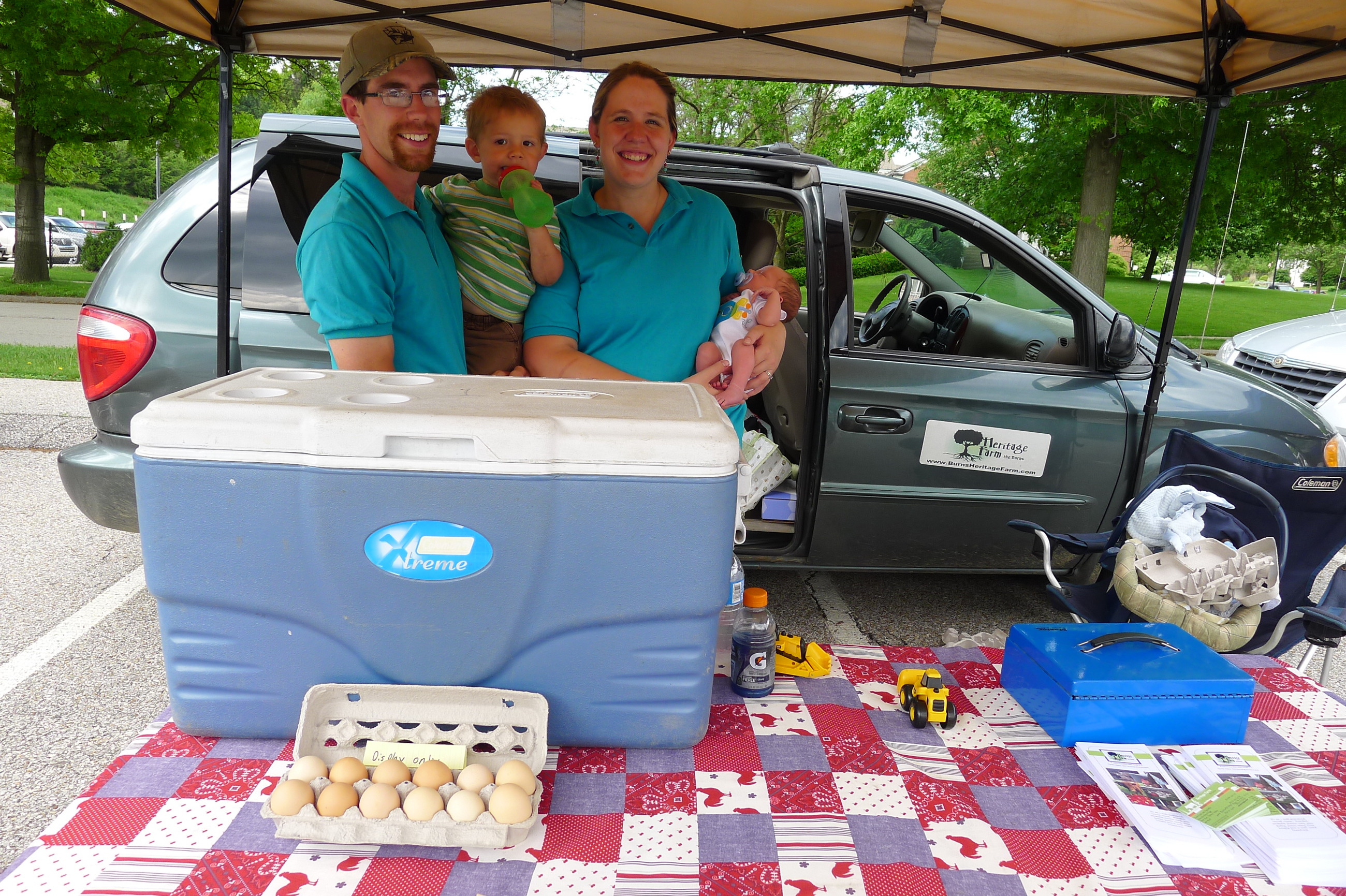P1230871-18 The Burns family drove from their Heritage Farm in Ridgway about 2 1/2 hours away: Pete, with Micah, 2, and Patrick, 10 days old, and wife Tara at opening day at the Upper St. Clair Farmers Market on May 29.