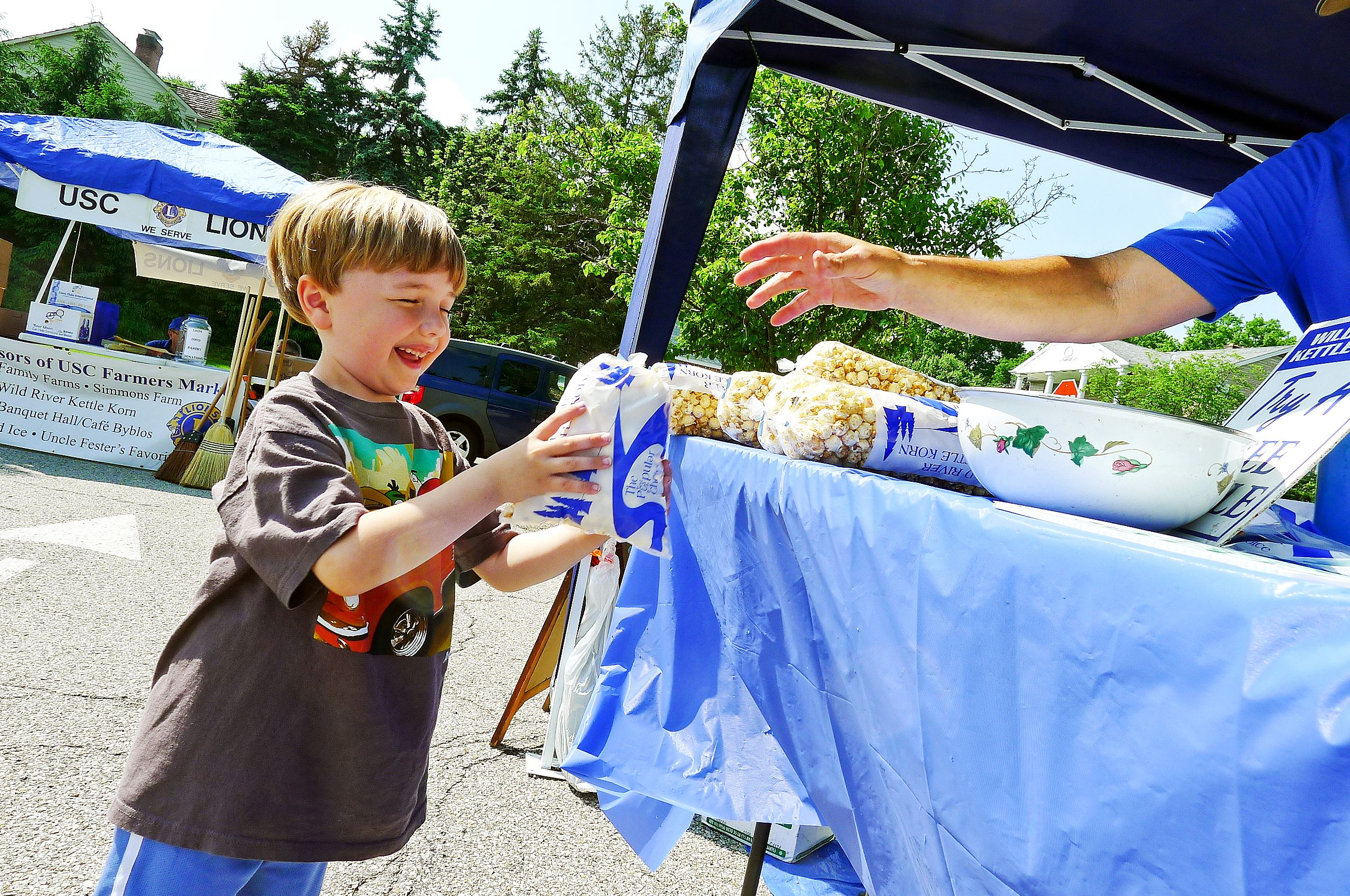 P1230817-14 Hudson Honeycutt got a snack from Wild River Kettle Korn at opening day at the Upper St. Clair Farmers Market on May 29.