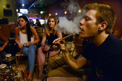 In this 2014 file photo, Maura DiDomenicus, 20, of Shaler, Roxy Oglesby, 20, of Eighty Four, and Mike Sweeney, 21 of Shaler, use a hookah to smoke flavored tobacco at Hookah Bookah Cafe on the South Side.